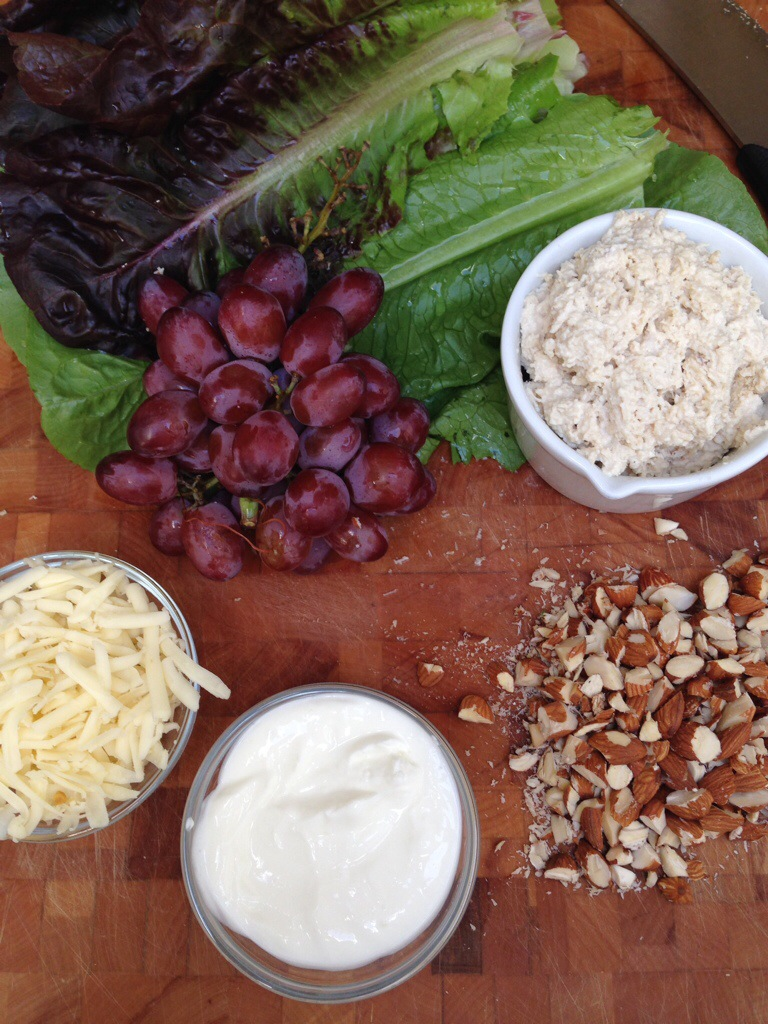 Lettuce, cheese, yogurt, grapes and nuts ingredients on table for salad