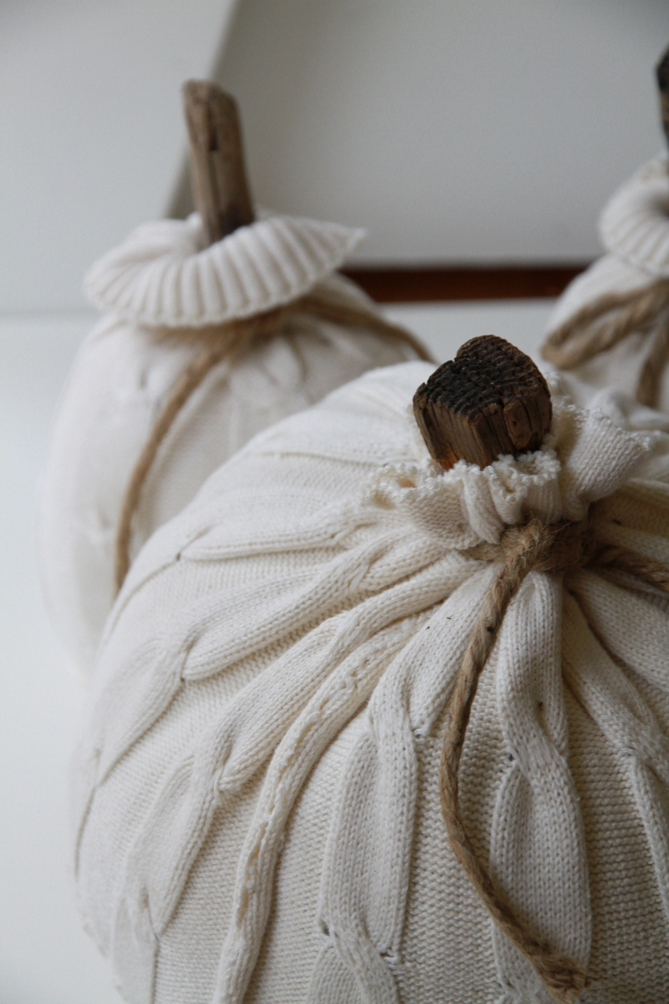 White sweater pumpkin with twill wrapped around the top.