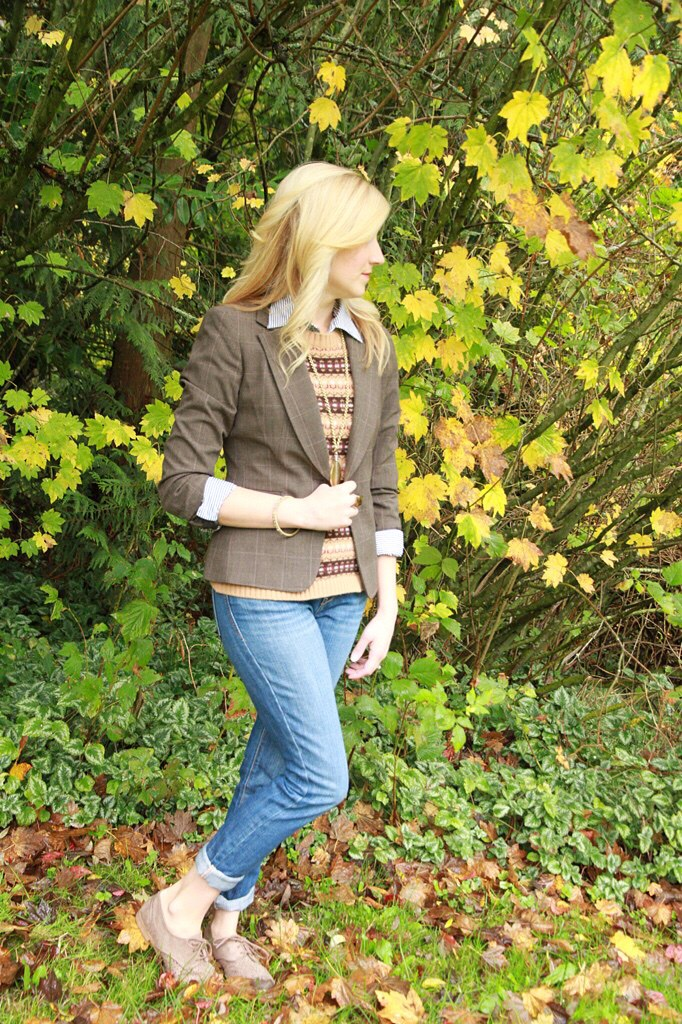 Blonde woman posing in front of bushes.
