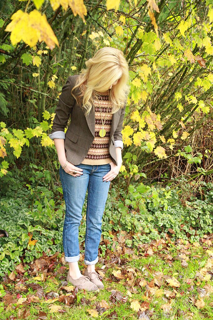 Woman standing in leaves with jeans, a blazer and sweater on.