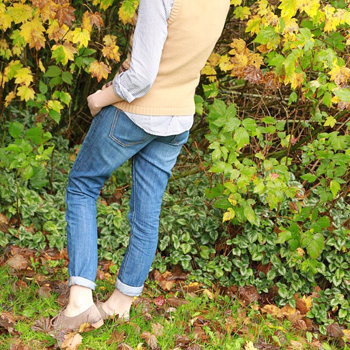 The back view of the woman standing by bushes with jeans on.