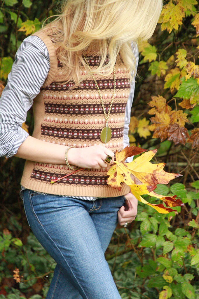 Woman with her jacket off and just a sweater and jeans holing a leaf.