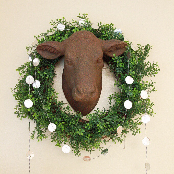 A metal head of a bull with a green wreath around it and a foil garland.
