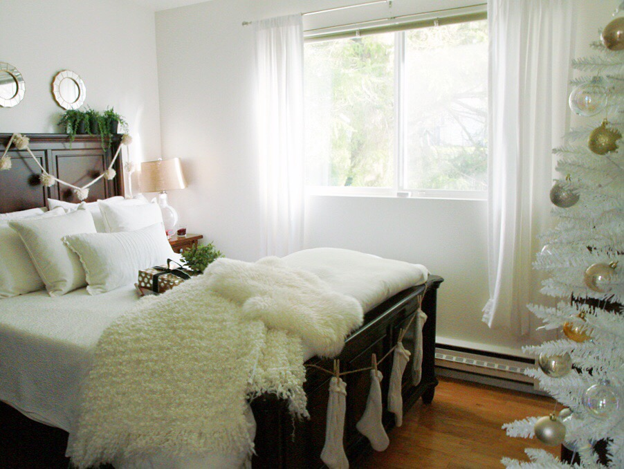 The white bedding with dark wood bed and faux fur on the bed.