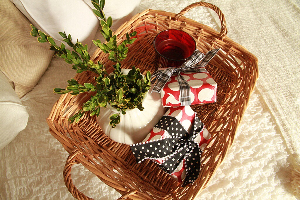 A wicker basket filled with presents and a green plant.