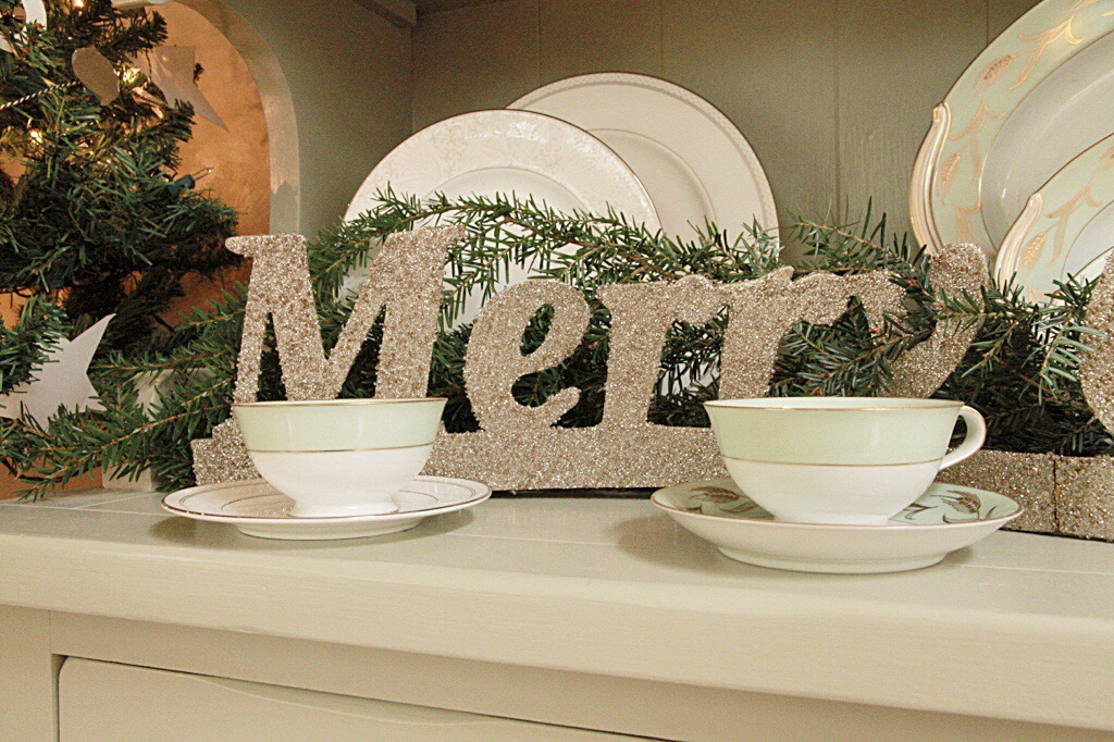 A Merry sign on the counter behind tea cups.