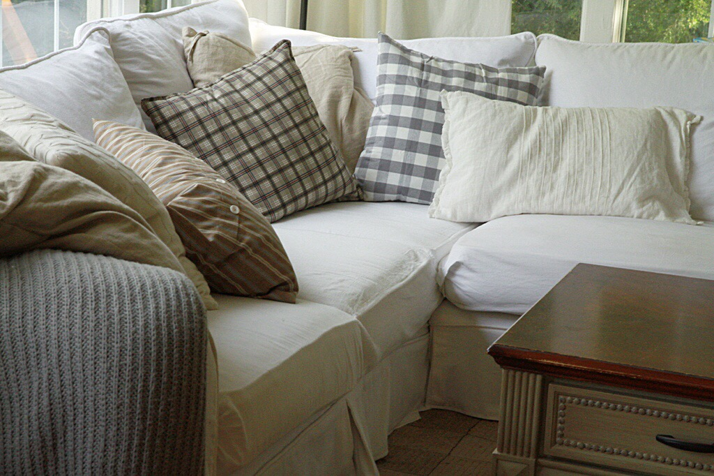 A white couch with gray and white pillows on it.
