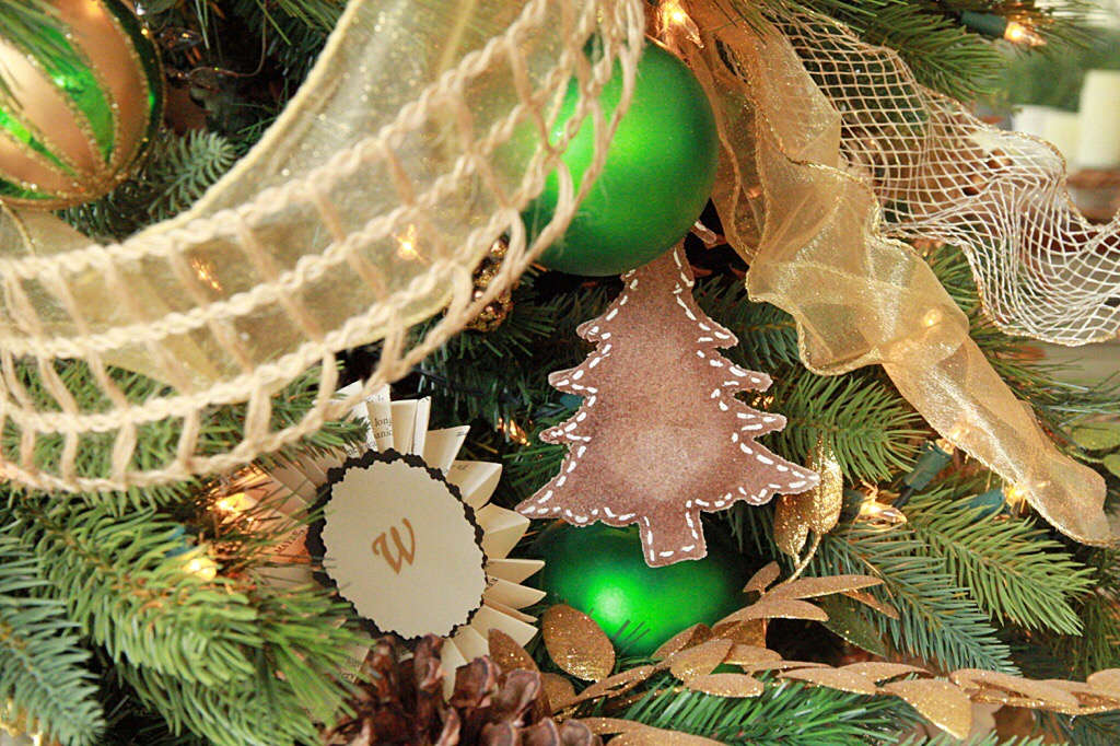 Green and gold ornaments on the Christmas tree.