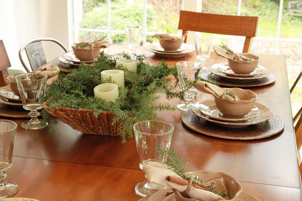 A centerpiece with evergreen and candles on a set table.