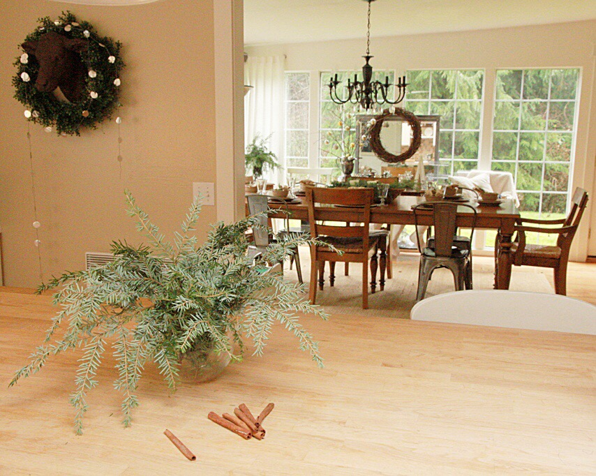 Dining room table with a wreath on the wall, and evergreen on the table.