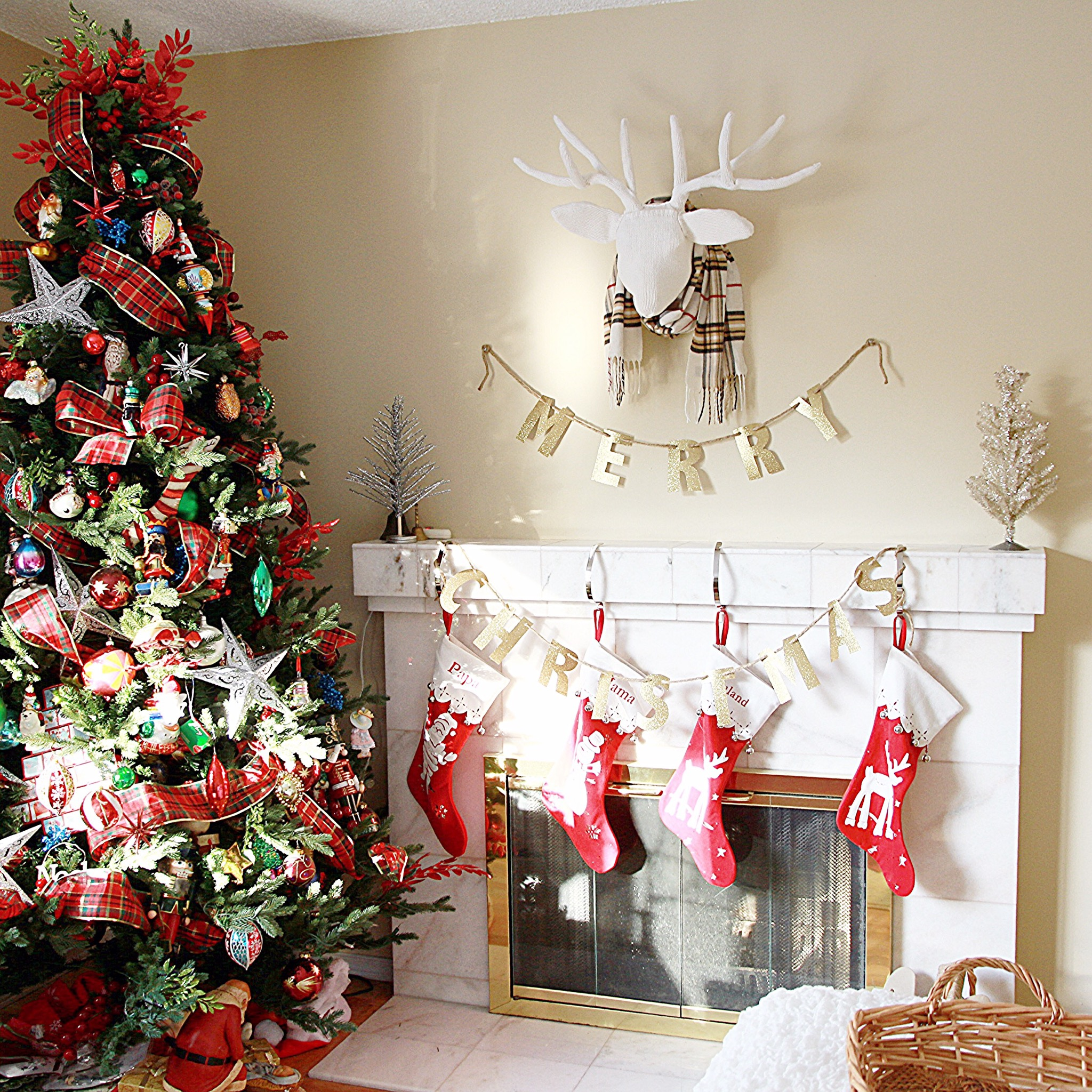 A white fireplace with antlers overhead and a large Christmas tree in the corner.
