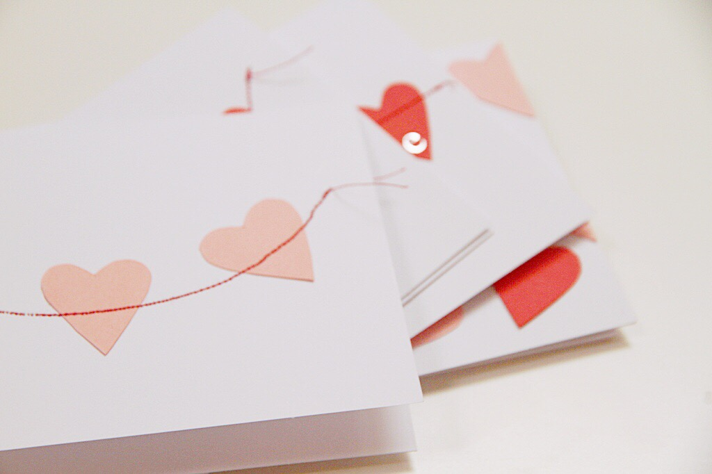 Light pink hearts on the white card with a thin red line running through it.