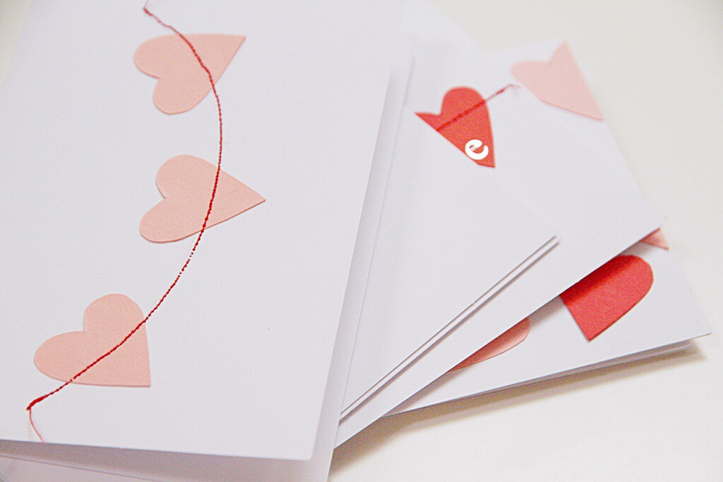 A white card stock with blush pink and red hearts on them.