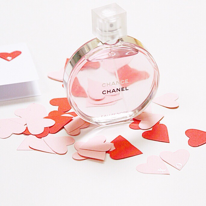 A Chanel perfume bottle on the counter with red hearts around it.