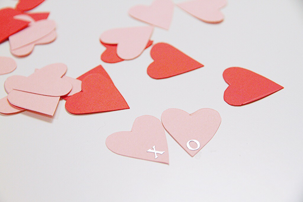 Light pink and red heart cutouts with an x and an o on two of the pink ones.