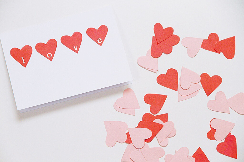 White card with red love hearts and the word love spelled out on it.