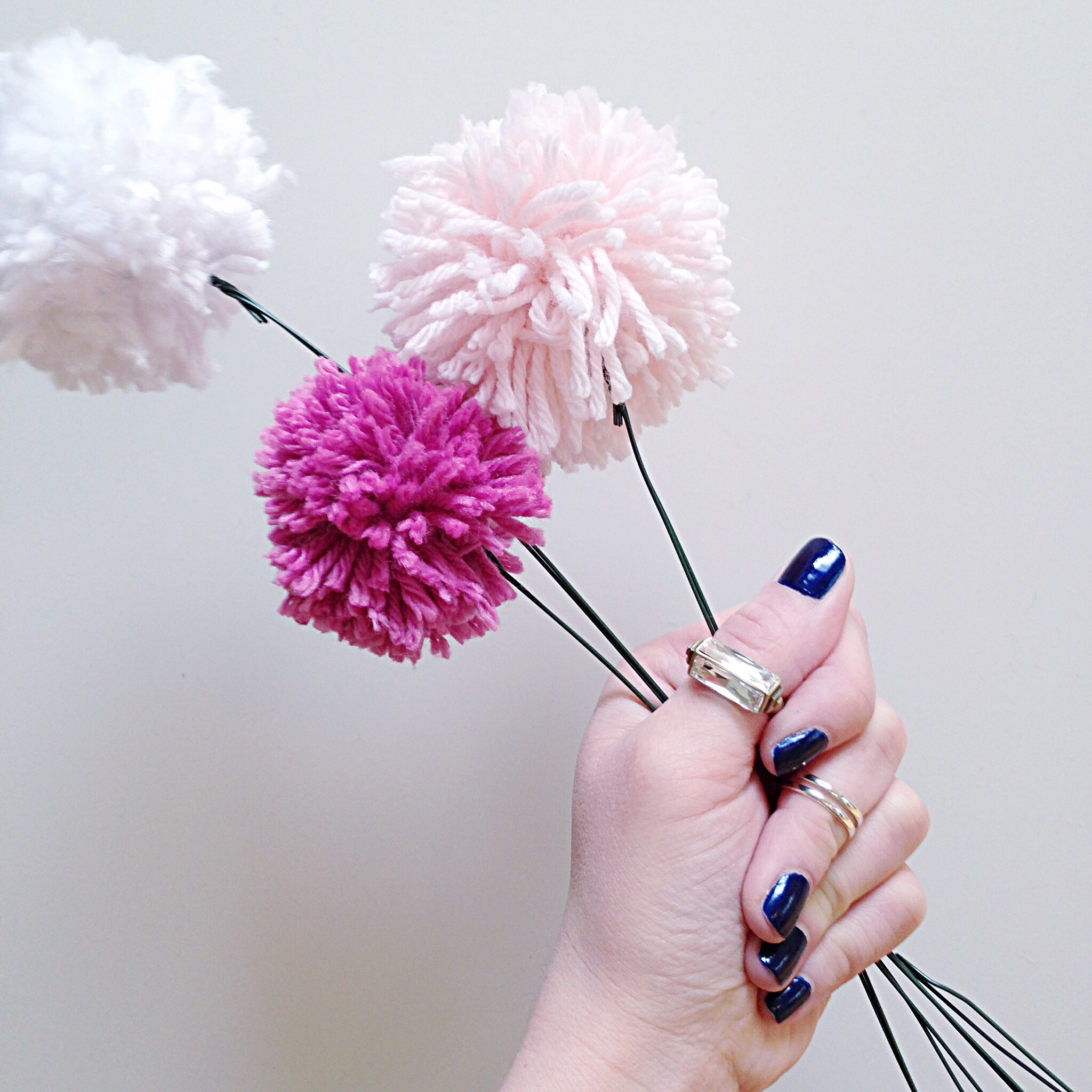 The Pom Pom flowers in a persons hand who has blue nail polish.