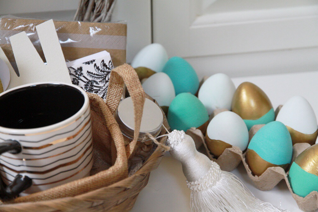 Painted Easter eggs in a egg box, with a wicker basket beside them.