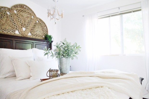 A bedroom with white bedding, a wooden headboard and a woven rug above it.