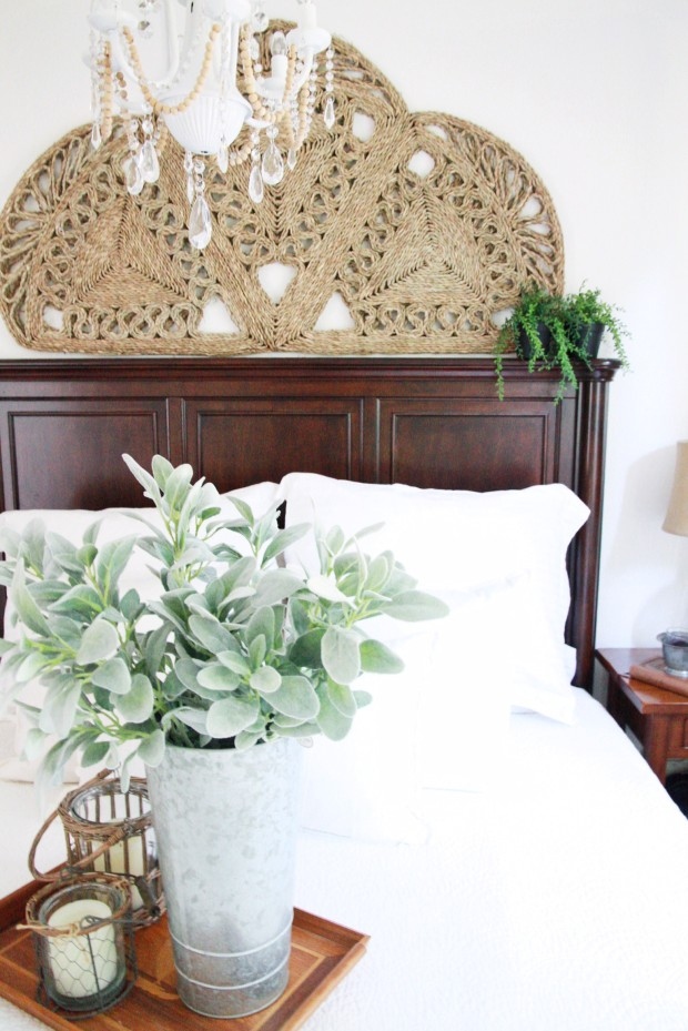 A woven rug above the headboard, a chandelier and a tray with candles and a plant on it.