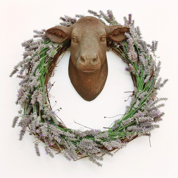 A plaster deer head with the wreath hanging around it.