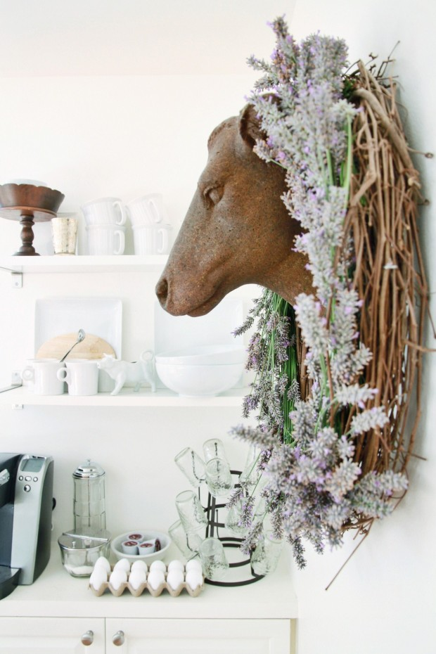 DIY lavender wreath hanging around the head of a deer on the wall.