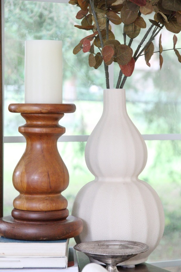 White vase with leaves and a wooden candle stick holder with a white candle in it.