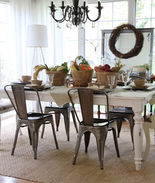 Dining room decorated for Thanksgiving with a wreath by the window, wooden buckets full of vegetables and pumpkins on the table.