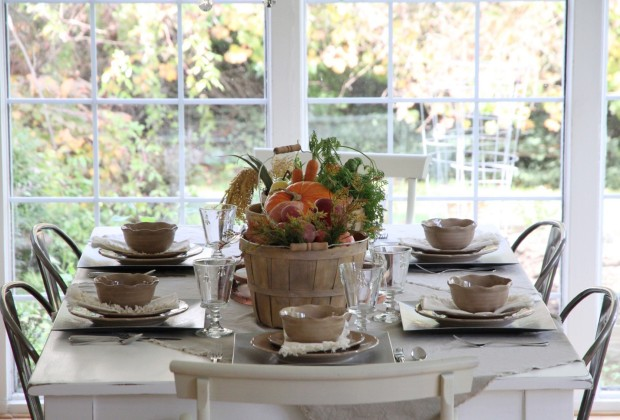 Large window with a dining room table in front of it set for Thanksgiving dinner.
