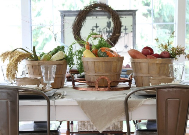 3 buckets filled with vegetables on the table with a wreath behind it.