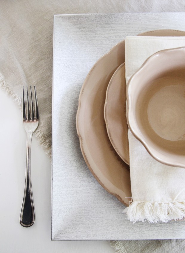 The charger, and then two plates, a napkin and bowl on top of the table.