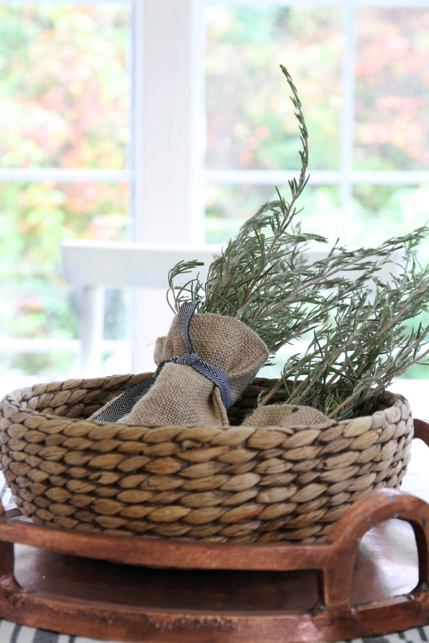 A wooden basket filled with burlap sacks and succulents wrapped in it.