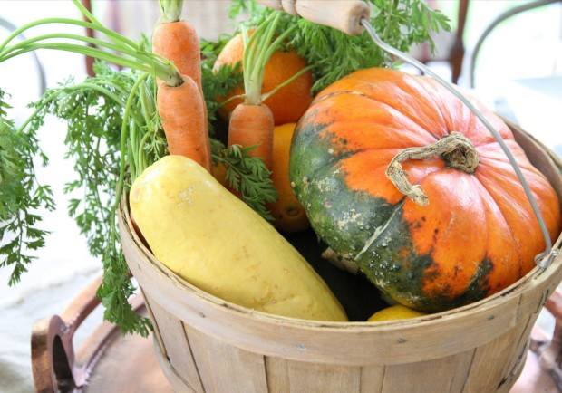 A wooden bucket with pumpkins, potatoes and carrrots.