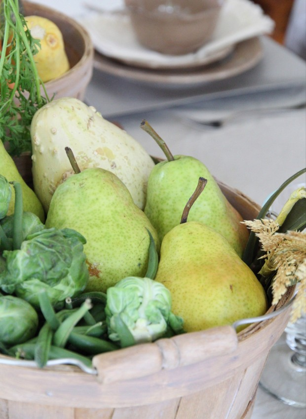 Pears and brussell sprouts in a wooden bucket.