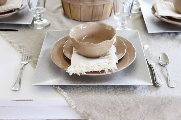 Square chargers with light brown bowls and plates on top.