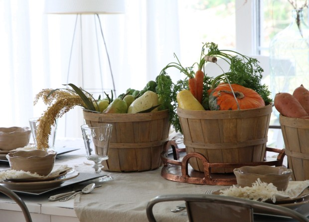 Wooden buckets filled with carrots, potatoes, and yams on the table as a centerpiece.