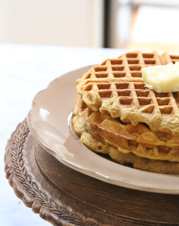 Close up picture of the cooked waffles with butter on top stacked on a plate.