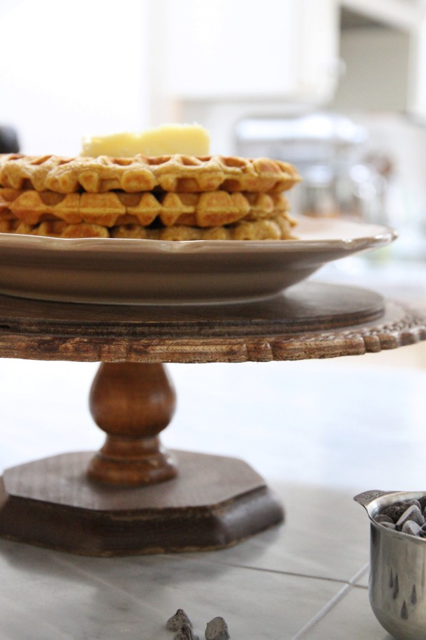 The wooden cake stand with pumpkin waffles on it, on the counter.