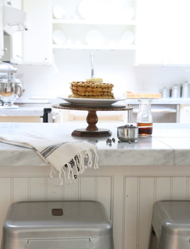 Kitchen island with silver stools beside it and waffles on the island.