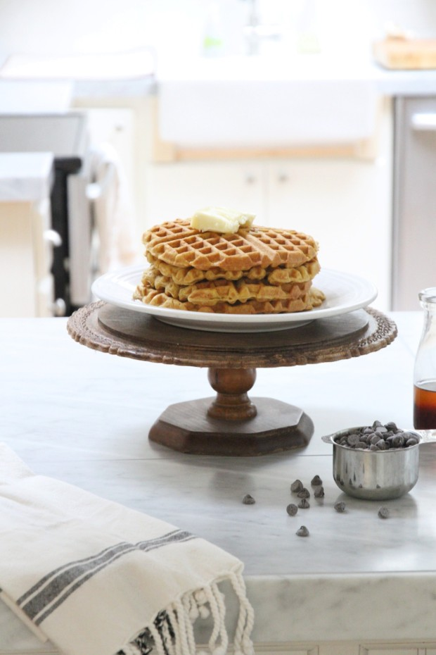 Waffles on a cake stand, with blueberries beside it and syrup.