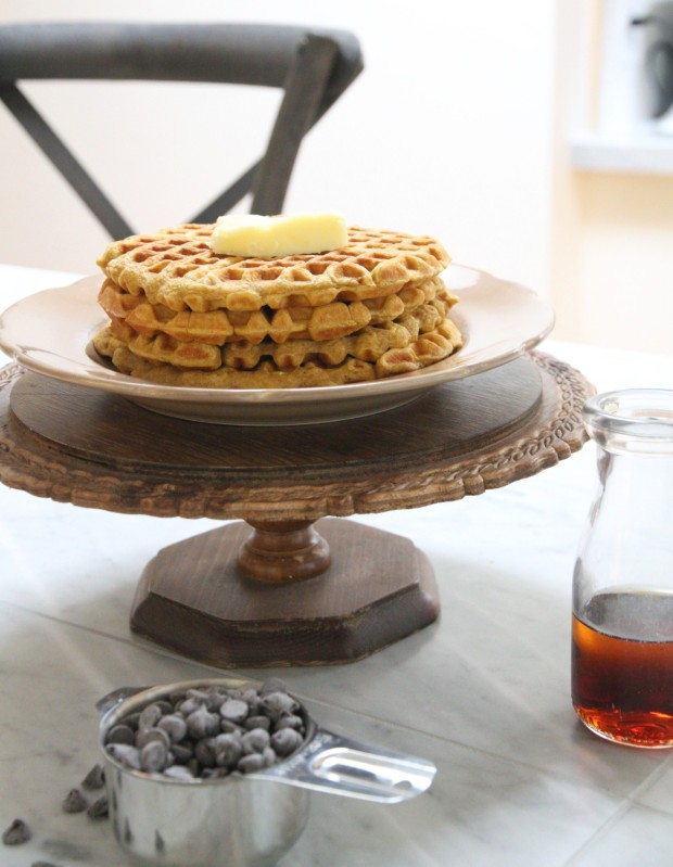 Stacked waffles on a wooden cake stand and butter on top of waffles.