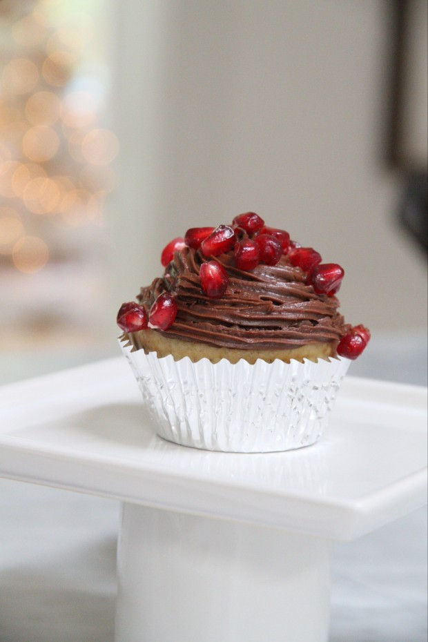 A white muffin covered in chocolate icing and pomegranates on top.
