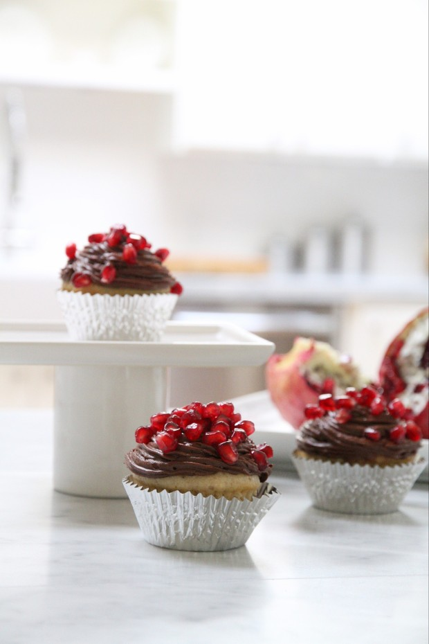 Two pomegranate muffins on the counter and one on a cake stand.