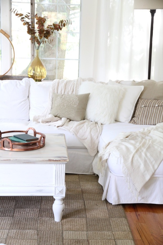 White coffee table on a cream colored rug, and a white couch.