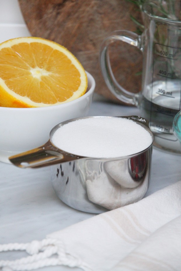 A measuring cup with sugar and a white bowl with half an orange in it on the counter.