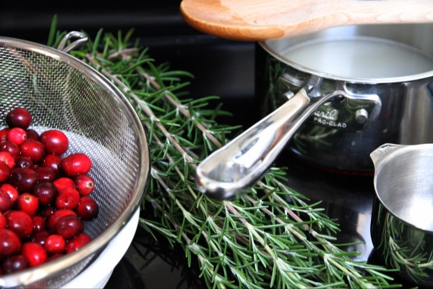 Cranberries in a strainer, and rosemary on the counter.