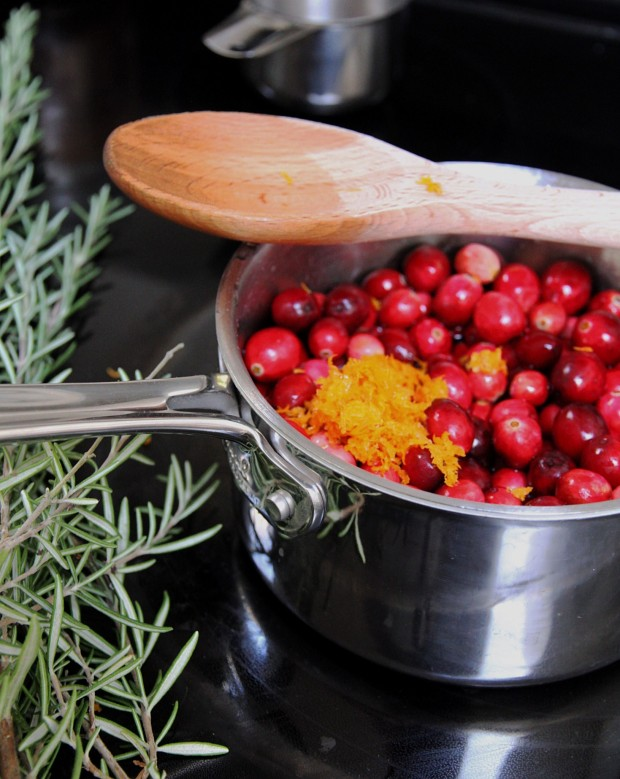 Cranberries on the stove top with orange zest in it and wooden spoon on the pot.