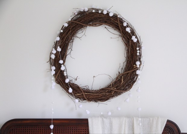 A natural twig wreath with white pom pom's on it.