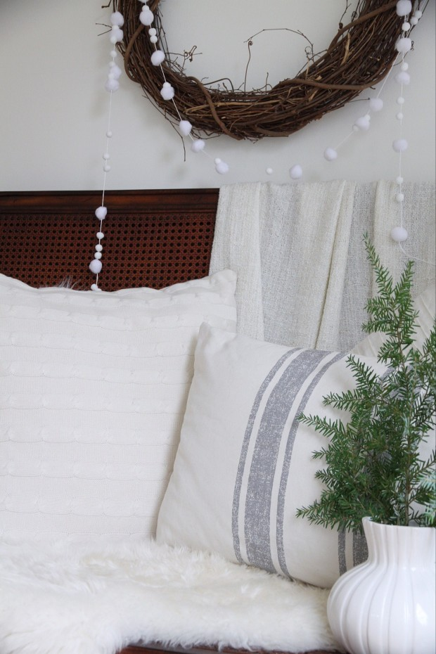 White bedding, a dark wood headboard, evergreen branches in a white vase and the wreath on the wall.