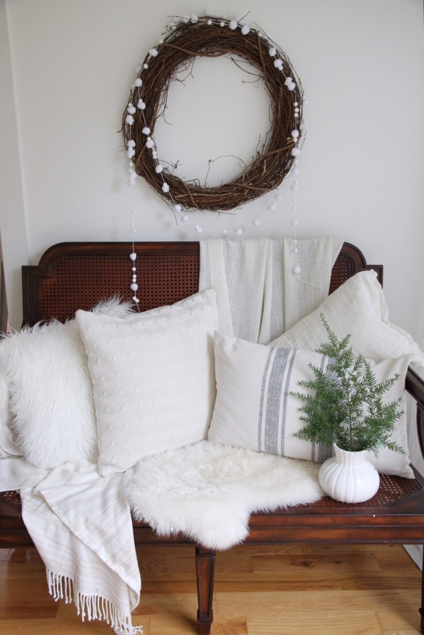 A wooden bench with white pillows ad blankets on it.
